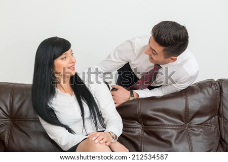 Half-length Portrait of young businessman  and his pretty colleague woman smiling to each other in office interior - stock photo