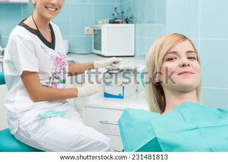 Half-length portrait of young fair-haired lovely smiling girl sitting on the dentist chair satisfied with the end of treatment and the doctor writing something behind her patient - stock photo