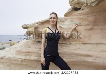Half length portrait of young female runner enjoying her recreation time during workout training outdoor in the mountain landscape, smiling sportive woman having rest after run outdoors along seashore - stock photo