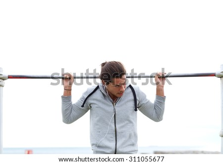 Half length portrait of young handsome man performs sport exercises to strengthen biceps muscles, male athlete doing pull ups on horizontal bar  in a cloudy day while listening to music on headphones - stock photo