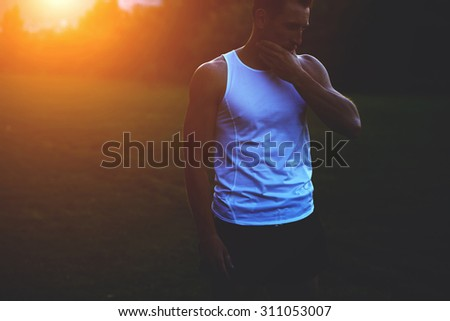 Half length portrait of young muscular build man taking break after evening run outdoors at sunset, handsome male athlete in copy space t-shirt for your text message or advertising content - stock photo