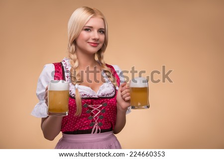 Half-length portrait of young sexy smiling blonde wearing pink dirndl and white blouse holding in both hands beer mugs looking at us. Isolated on dark background - stock photo