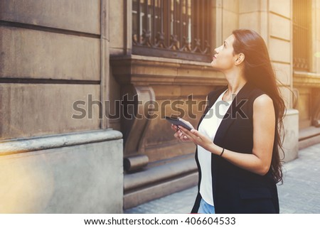 Half length portrait of young woman tourist using touch pad for navigation while lost the way during walking, female wanderer is using digital city map on her tablet computer during strolling outside - stock photo