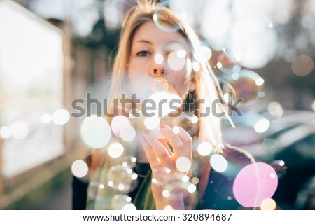 Half length profile of young beautiful hipster sporty blonde woman in town playing with bubble soap, looking in camera, blowing - childhood, happiness, carefreeness concept - backlight - stock photo