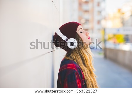 Half length profile portrait of young handsome caucasian blonde hair woman leaning against a wall, listening music with headphones, eyes closed - serene, enjoying, music concept - stock photo