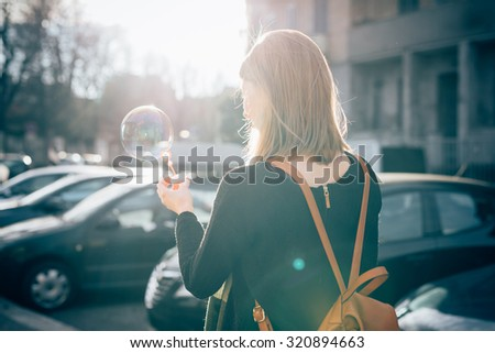 Half length view from back of young beautiful hipster sporty blonde woman in town playing with bubble soap - childhood, happiness, carefreeness concept - backlight - stock photo