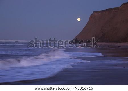Half Moon Bay at moonset and sunrise coinciding - stock photo