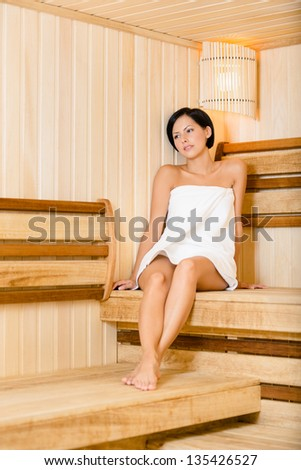 Half-naked lady relaxing in sauna. Concept of self-care, health and relaxation - stock photo