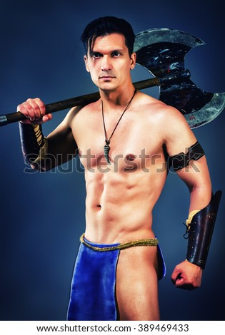 half naked man in the image of ancient warrior on blue background. - stock photo