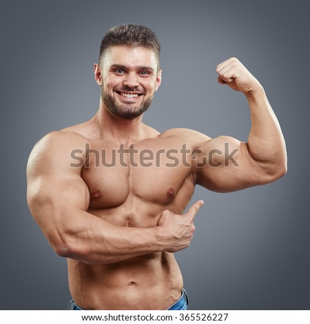 Half naked sexy body of muscular athletic man. Smiling bodybuilder pointing to his strained biceps muscle. - stock photo