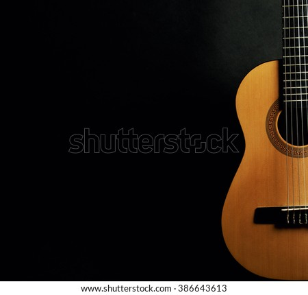 Classical guitar Stock s & #0: stock photo half of a bright yellow acoustic guitar on a black background with copy space