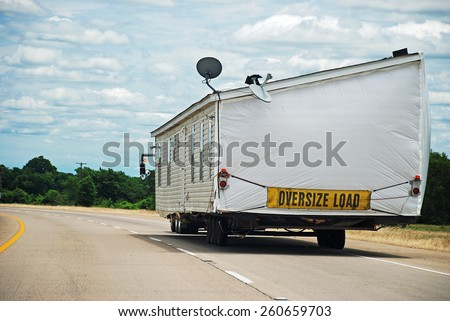 Half of double wide modular home being transported along interstate highway. - stock photo