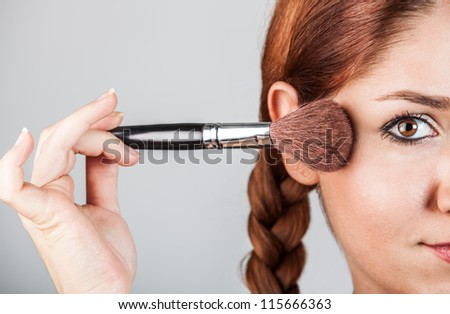 half of face portrait of a woman putting on makeup with a blush brush - stock photo