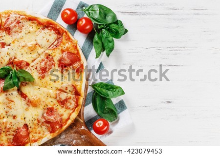 Half of Hot true PEPPERONI ITALIAN PIZZA with salami and cheese. TOP VIEW Tasty traditional pepperoni pizza on board on white wooden table. Copy space for your logo. Ideal for commercial  - stock photo