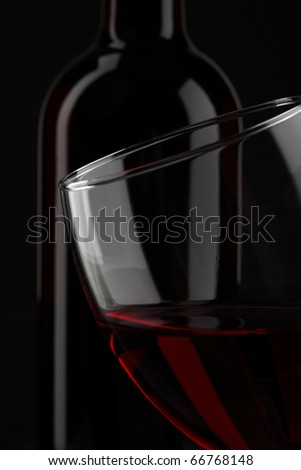 half of red wine glass isolated on black background - stock photo