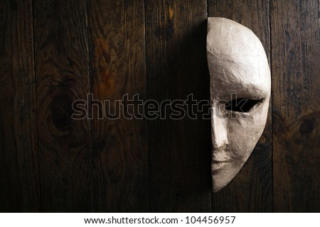 half of the paper masks on a wooden background - stock photo