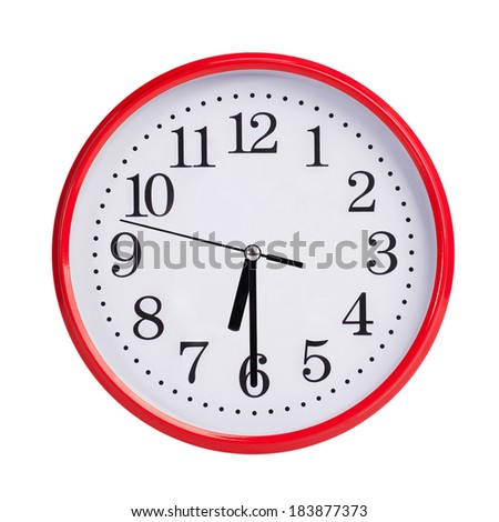 Half of the seventh on a red round clock face - stock photo
