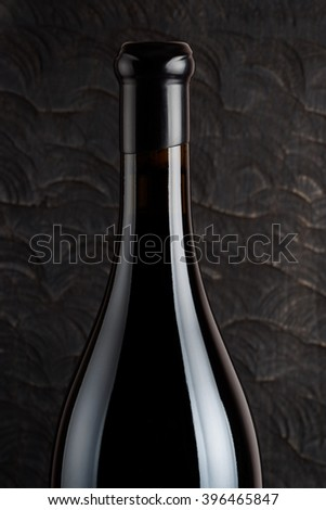 Half of wine bottle, old wood in background - stock photo