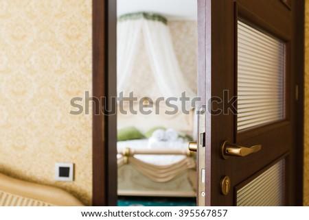 Half opened door of a bedroom. Hotel bedroom door half open. Hotel room welcome guests. Opening door closeup. Door handle. Privacy, intimacy concept. Entrance to the hotel bedroom.  - stock photo