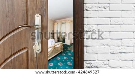 Half opened door to a bedroom. Door handle, door lock. Lounge door half open. Opening door. Welcome, privacy concept. Entrance to the room. Door at white brick wall, modern interior design. - stock photo