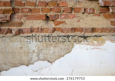 Half painted red brick wall copyspace. Rough weathered wall brick half covered with cement concrete and white paint. Very good background for inscriptions or as part of design. - stock photo