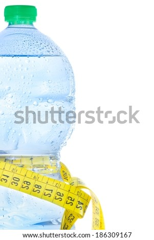 half plastic bottle with water, drops and measuring tape on white background, concept of fitness and diet with space for text - stock photo