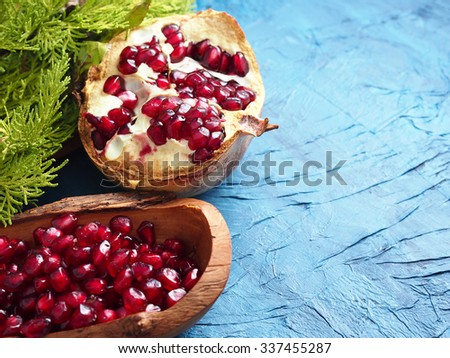 Half pomegranate  and pomegranate seeds in a wooden bowl and a branch of spruce on dark blue background - stock photo