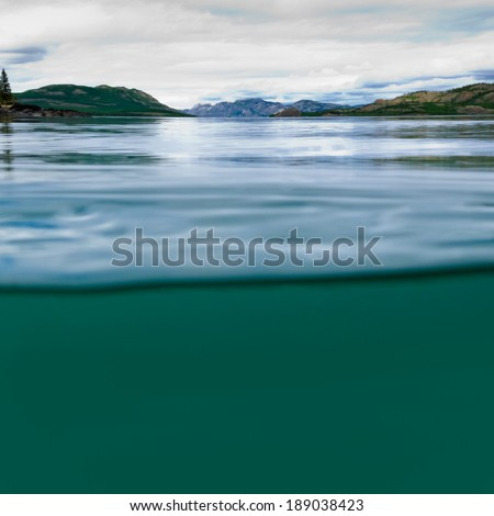 Half underwater half over, over-under split shot of huge Lake Laberge, Yukon Territory, Canada, clear blue freshwater and distant shore boreal forest taiga landscape - stock photo