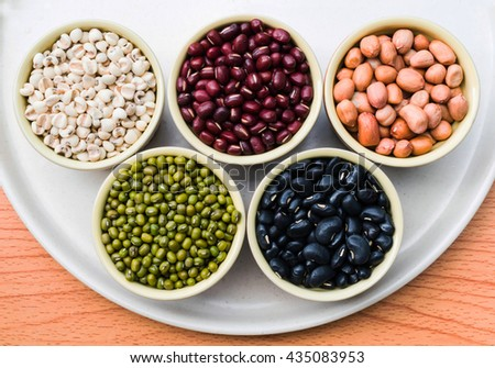 half view selected focus Red beans , Black beans, Green beans,Millet,lotus seeds,peanut, healthy organic seeds in round ceramics cups on a plywood table - stock photo