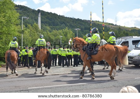 HALIFAX, WEST YORKSHIRE, ENGLAND-JUL 10: Riot Police on horses face demonstrators of the EDL (English Defence League) organised rally on July 10, 2010 in Halifax, West Yorkshire - stock photo