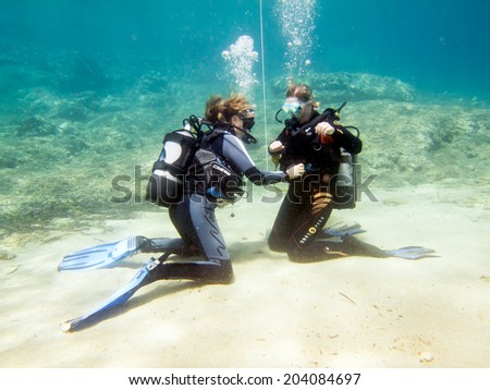 HALKIDIKI,GREECE-JULY 09 2014 : Two female scuba divers practise their skills underwater before a dive.Scuba diving is a sport carried out in many places around the world - stock photo