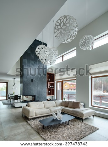 Hall in a modern style with light walls and big white round decorative lamps at the top. In the centre there is a beige sofa with pillows and plaid, dark table with three decorative vases, two black - stock photo