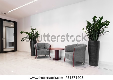 Hall of corporate building with comfortable armchairs - stock photo