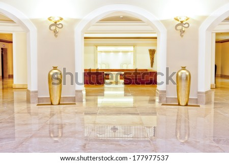 Hall or foyer with a marble floor and arches flanked by ornamental gold urns and ornate up-lighters in a luxury building interior - stock photo