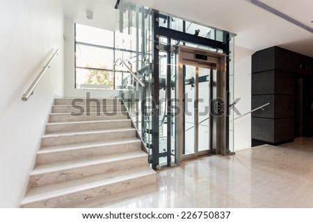 Hall with staircase and elevator inside the building - stock photo