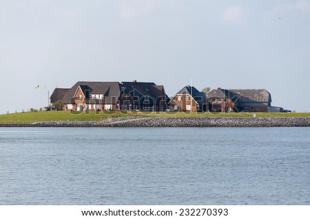 HALLIG LANGENESS, GERMANY - MAY 19. Restaurant and Dwellings on the Warft on the Hallig Langeness in north Frisia on May 19, 2014. The Hallig is located in the wadden sea in north Germany. - stock photo