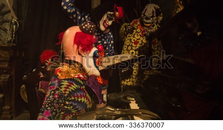 Halloween. A group of clowns having fun around the piano. Clown playing the piano. - stock photo