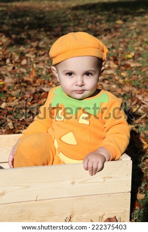 Halloween baby dressed as a pumpkin amongst fall leaves - stock photo