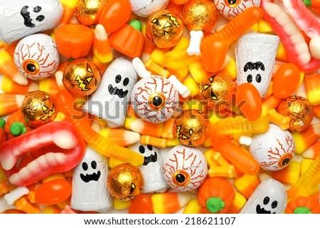 Halloween background of mixed candies, orange color theme - stock photo