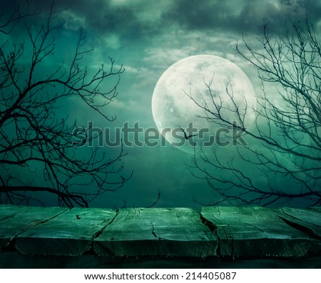 Halloween background. Spooky forest with full moon and wooden table - stock photo