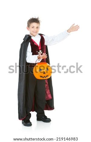 Halloween: Boy Vampire Gestures To Side While Holding Candy Bucket - stock photo