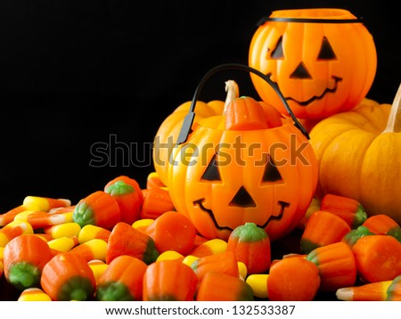 Halloween candies spilled on black background. - stock photo