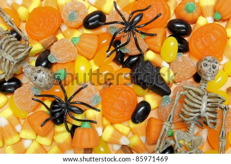 Halloween candy background with jellies, candy corn, and toy spiders and skeletons - stock photo