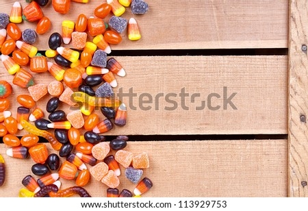 Halloween candy scattered on a wooden crate - stock photo