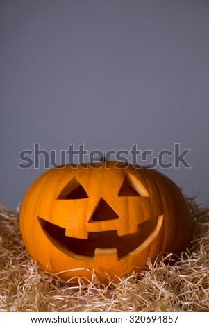 Halloween concept - close up of pumpkin Jack-O-Lantern over grey background - stock photo