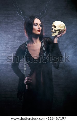 Halloween concept: young and sexy witch makes the witchcraft in the dungeon - stock photo