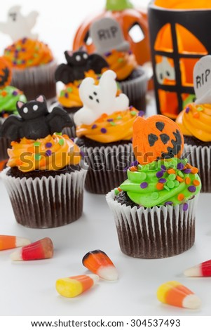 Halloween cupcake with jack-o'-lan���·tern and bat decorations surrounded by Halloween cupcakes, corn candies, and decoration.  - stock photo