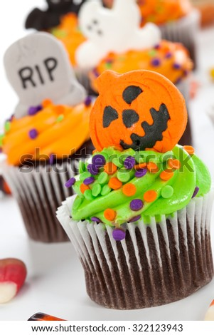 Halloween cupcake with jack-·tern and bat decorations surrounded by Halloween cupcakes, corn candies, and decoration.  - stock photo