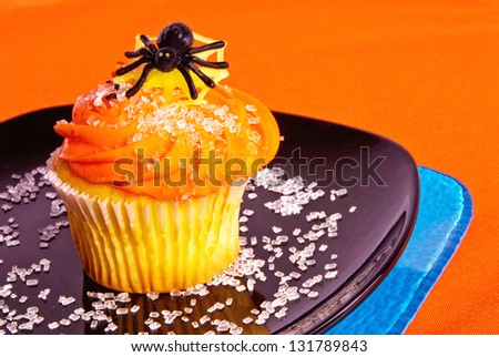 halloween cupcake with orange icing and a toy plastic black spider on top. Stacked royal blue and black colored plates with candy sprinkles. Bright orange background.  - stock photo
