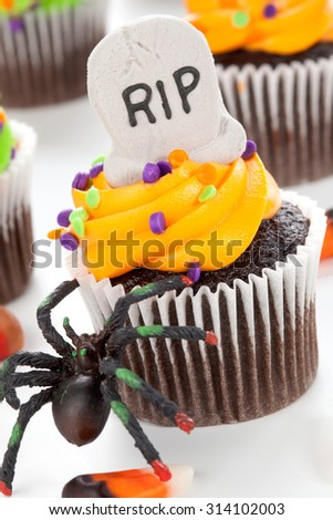 Halloween cupcake with RIP, ghost, and bat decorations surrounded by Halloween cupcakes, corn candies, and decoration. - stock photo